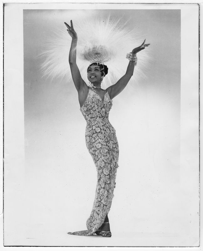 Josephine Baker stands with arms raised wearing an evening gown and headdress