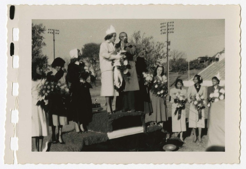 Outdoor view of women standing on podium with bouquets, and a man with a microphone on a football field.