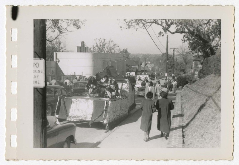 Outdoor view of homecoming parade, women seated on float with spectators walking down the street.