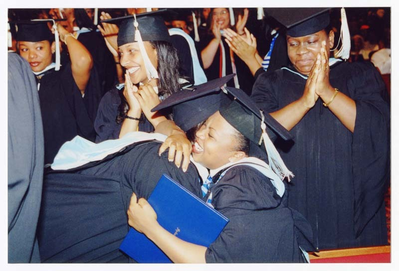 View of two graduates embracing surrounded by fellow graduates.