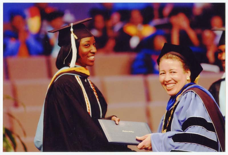 View of Beverly Tatum handing diploma to graduate and posing for photograph