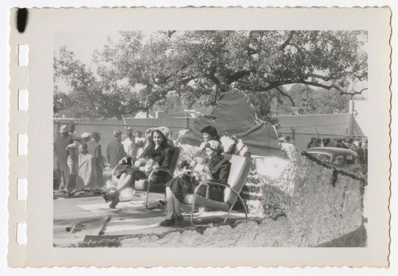 Outdoor view of homecoming parade with women seated on a float.