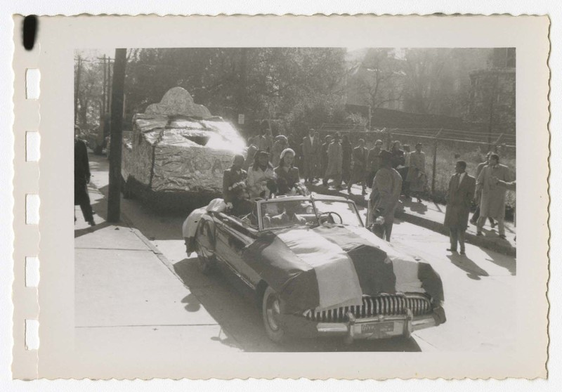 Outdoor view of homecoming parade with women sitting in a car with a float.