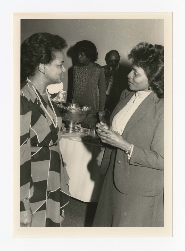 "Indoor view of two women. Written on verso: ""First Lady Carrie Smith chats with an acquaintance at a reception c. 1986""."