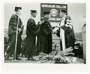 President Hugh Gloster on stage during Commencement with Dr. Lee, Dr. Franklin Forbes, and Rev. Martin Luther King Sr.. Written on verso: Commencement 1969 Lee, Forbes, King Sr. and Gloster