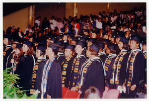 Graduates standing at commencement.
