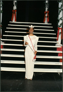 Unidentified Homecoming queen wearing a white gown, crown, and sash stands in front of stairs