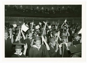 View of group of graduates cheering at commencement.
