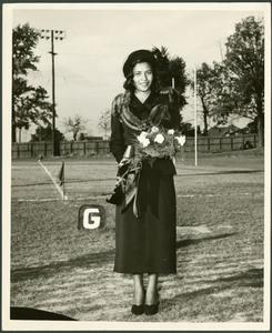 Homecoming Miss Clark-Ruth Woodard stands outside on an athletic field wearing a dark coat and hat holding a bouquet of flowers