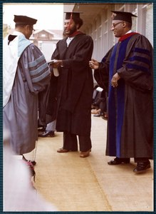 An unidentified man receives his degree from ITC president Dr. Grant S. Shockley (left), as Dean Wilkerson (right) watches.