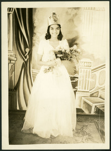 Unidentified Homecoming queen wears a homemade crown and white dress holding a bouquet of flowers