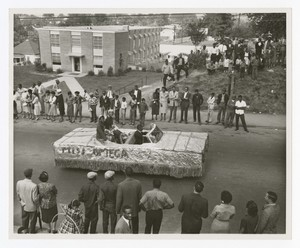 """Street view of women seated on a convertible parade float """"Miss Omega""""."""