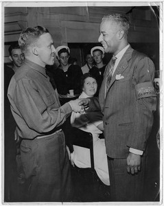 Harold Jackman shakes a man's hand while a seated woman looks at them from the background and young sailors stand behind her