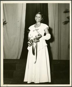 Homecoming Miss Clark-Jane Brady wears a white dress holding a bouquet of flowers
