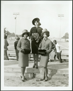 Three women stand in front of an athletic field; one in a dark coat and hat stands on a platform holding a bouquet while two stand in front of her wearing matching coats, hats and fur muffs.