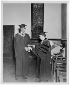 Dr. Harry Richardson awards a man a diploma and shakes his hand during commencement. Written on verso: Reverend Clifton N. Bonner, 1953 graduate of Gammon, received award from president Harry V. Richardson for outstanding achievements during his three years as a student at Gammon.