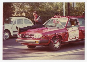 """Street view of a man seated on hood of car with poster """"Clark College Presents Bobby Brown..."""""""