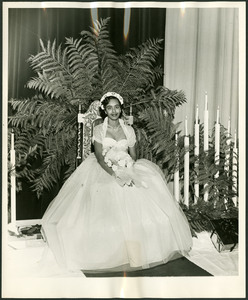 Homecoming Miss Clark-Jacqueline Laughlin seated on a throne wearing a white dress and holding a bouquet of flowers