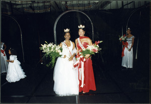 Two unidentified Homecoming queens wearing white and red gowns and crowns, holding bouquets, smile for the camera while 2 unidentified women and young girl stand in the background