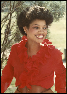 Unidentified Homecoming queen smiles looking away from camera while wearing a ruffled red blouse and brown belt.