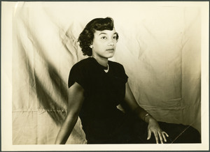 Unidentified Homecoming queen is pictured seated wearing a black dress and pearls looking to the right of the camera