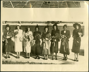 Exterior picture of 8 women wearing coats and hats and carrying bouquets.