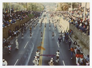 Street view of a marching band, people seated on walls on either side.
