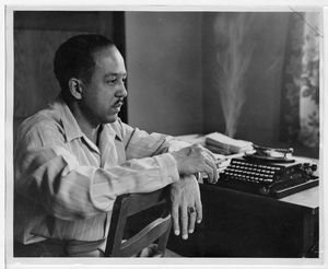 Langston Hughes seated backwards on chair smoking a cigarette in front of his desk and typewriter
