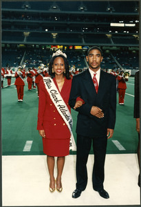 Unidentified Miss Clark Atlanta University queen wearing a red suit and crown stands arm-in-arm with an unidentified man in a suit in front of the marching band