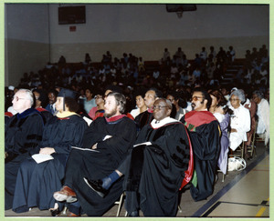 Professors and audience members watch a commencement address being delivered.