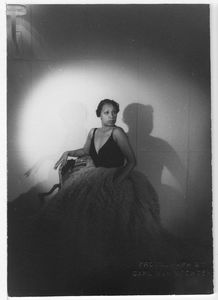 Josephine Baker seated wearing evening gown