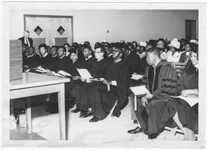 A graduating class awaits to receive their diplomas.