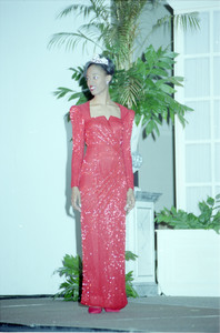 Unidentified Homecoming queen wearing red gown and tiara stands in front of a plant on stage