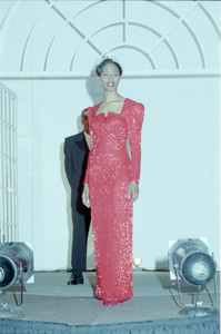 Unidentified Homecoming queen standing on stage wears a red gown and tiara; an unidentified male stands behind her