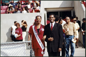 Unidentified Miss Clark Atlanta University homecoming queen wearing a red suit and crown stands arm-in-arm with an unidentified male in a suit in front of the stands at the stadium