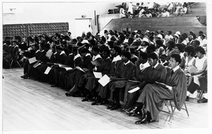 People gather in a gymnasium for a commencement ceremony.