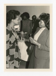 """Indoor view of two women. Written on verso: """"First Lady Carrie Smith chats with an acquaintance at a reception c. 1986""""."""