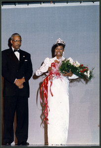 Unidentified Homecoming queen smiles for the camera wearing white gown, crown, and holding a large bouquet. An unidentified older man wearing a tuxedo stands to her right.