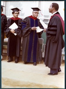 An unidentified man walks as Dean Wilkerson (background right) and unidentified man watch during commencement.