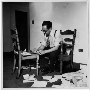 Langston Hughes seated in chair smoking while writing in a notepad using another chair as a desk