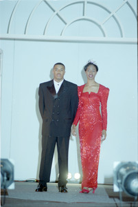 Unidentified Homecoming queen wears a red gown and tiara, standing next to unidentified male wearing  a tuxedo