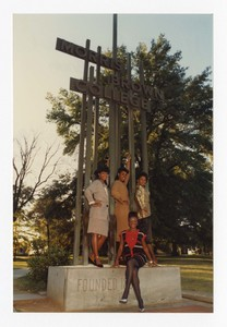 """Outdoor group portrait of four women standing on sculpture sign """"Morris Brown College""""."""