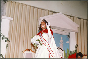 Unidentified Homecoming queen smiles and waves while wearing a white gown, tiara, and red cape and holds a bouquet of flowers.